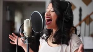 Angela Apigo sings into a recording mic with passion and a smile on her face.