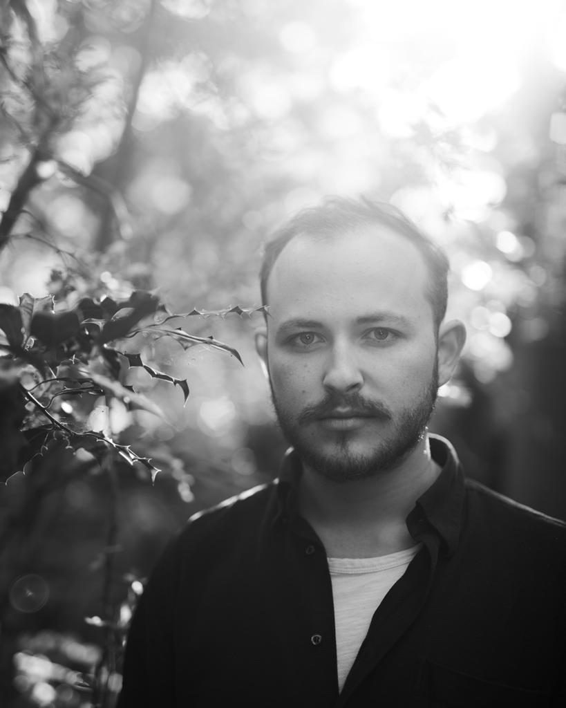 a black and white portrait of Kaine Francesco outdoors in the forest with the sun pouring over his shoulder